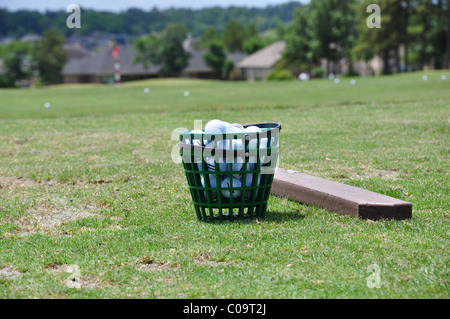 Bucket of golfballs on the driving range - Stock Photo