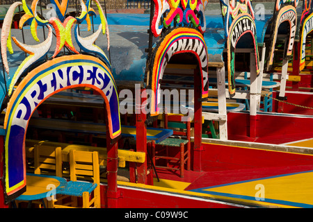 Colorful canal boats or trajineras await tourists at Xochimilco or 'the floating gardens' in southern Mexico City. - Stock Photo