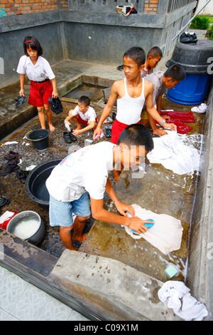 Children washing their school uniforms, Margaritha children's home, Marihat, Batak region, Sumatra island, Indonesia, - Stock Photo