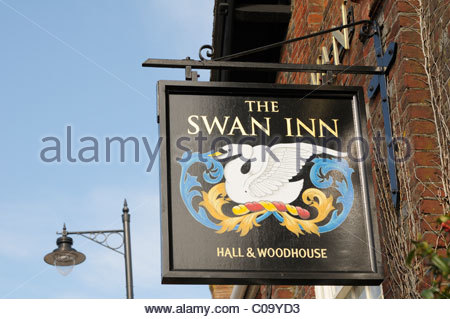 Looking up at the hanging sign for The Swan Inn public house sign in Sturminster Newton, Dorset, England - Stock Photo