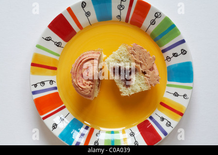 looking down on Marks & Spencer strawberry and vanilla cupcake cut in half on brightly coloured yellow plate - from - Stock Photo