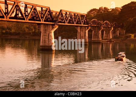 Saphan Mae Nam Khwae (Bridge on the River Kwai) at dusk, Kanchanaburi, Thailand - Stock Photo