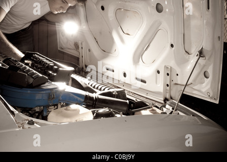 Man working on car by flashlight. Mechanic fixing auto, repair at night. - Stock Photo