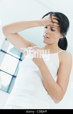 woman taking temperature with hand on forehead. Low angle view - Stock Photo