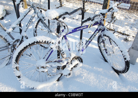 A bicycle parked in snow in Lochwinnoch Renfrewshire Scotland UK - Stock Photo
