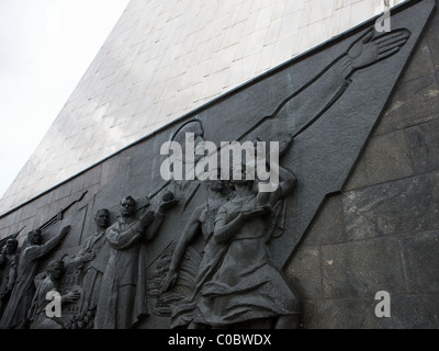 The base of the Space Obelisk monument, Moscow, Russia. Lenin leads the masses into space as a woman offers her - Stock Photo