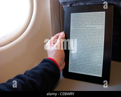 man reading an electronic ebook reader on board an aircraft - Stock Photo