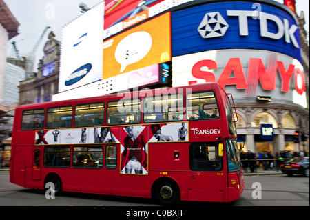 double decker red bus in front of the advertisings of Piccadilly circus, London, England, UK - Stock Photo