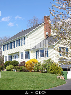 Yellow New England Style colonial house on a spring day - Stock Photo