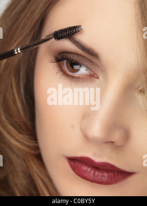 Closeup of a woman's face with makeup being applied to her eyebrows - Stock Photo