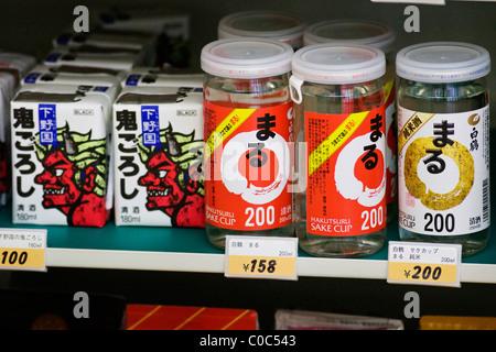 Various brands of sake for sale on a supermarket shelf in Tokyo, Japan - Stock Photo