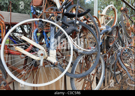 A collection of old and rusty bicycles and parts hung on a fence. - Stock Photo