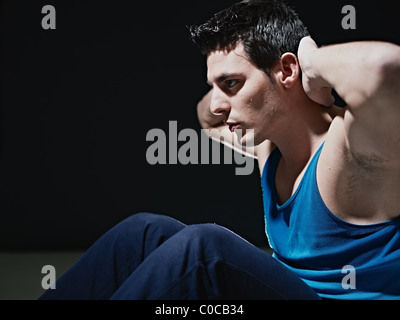 young adult caucasian male in blue sportswear exercising abdominals on black background, looking away. - Stock Photo