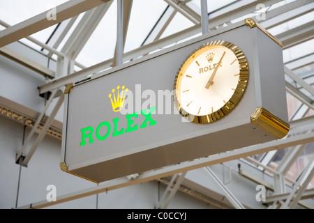 Display clock advertising Rolex brand of watches. International terminal departure hall, Geneva / Geneve Airport, - Stock Photo