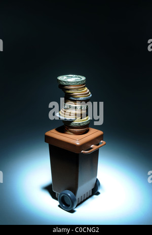 RUBBISH DOMESTIC WASTE WHEELY  WHEELIE BIN WITH MONEY RE COSTS OF RECYCLING GARBAGE  ENVIRONMENT RECYCLE  BIN MEN - Stock Photo