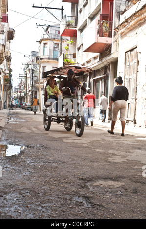 Typical back street scene with bicycle taxi Old Havana Cuba - Stock Photo