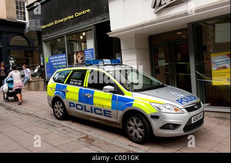 Silver police car parked outside shops on a street in Norwich, Norfolk, England. - Stock Photo