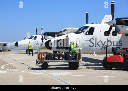 Offloading luggage from a Skybus Twin Otter at St.Mary's aieport Isles of Scilly - Stock Photo