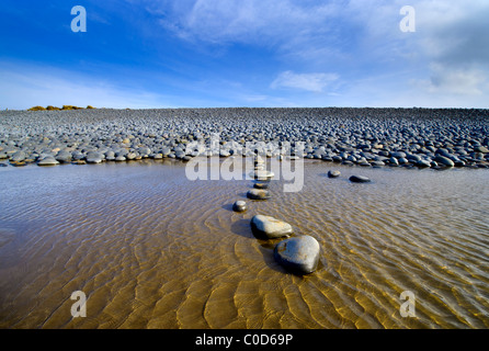 rounded pebbles stepping stones at Northam Burrows on the North Devon coast - Stock Photo