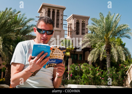 Tourist man reading a tourist guide of Dubai at Madinat Jumeirah with wind towers in the background, Dubai, United - Stock Photo