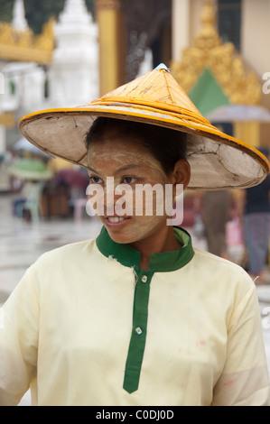 Myanmar (aka Burma), Yangon (aka Rangoon). Stupa Shewedagon, local woman with typical thanaka (natural sun cream) - Stock Photo
