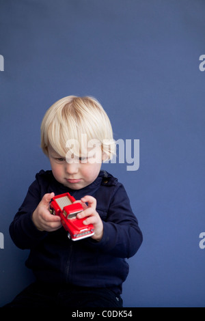 Little boy playing with red truck - Stock Photo
