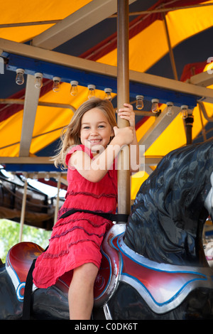 Little girl riding on the carousel - Stock Photo