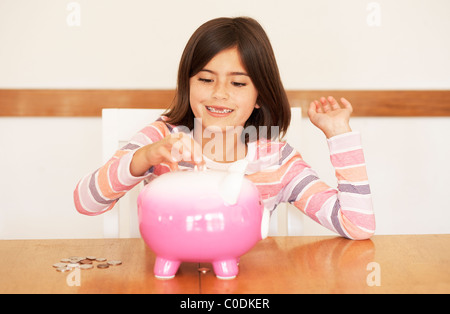 Little girl putting her money in a piggy bank - Stock Photo