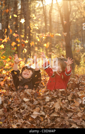 Little kids playing in fall leaves - Stock Photo