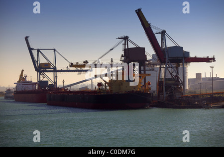 Cargo ships and tankers loading and unloading their cargos at an industrial port - Stock Photo