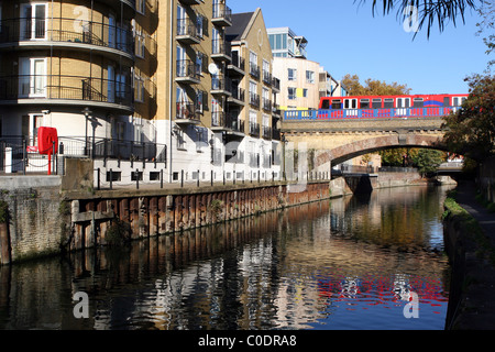 Docklands Light Railway Train crossing the Limehouse Cut canal, East London, UK. - Stock Photo