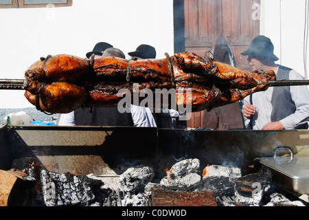 Whole pig roasting on barbecue at Fiesta del Almendro in Tejeda, Gran Canaria, Canary Islands, Spain - Stock Photo