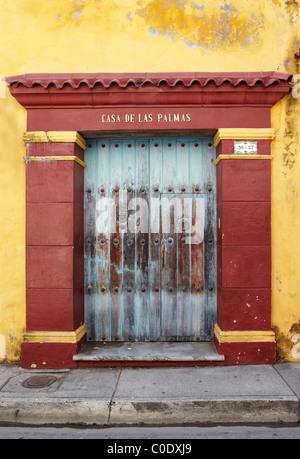 wooden front door on yellow colonial building - Stock Photo