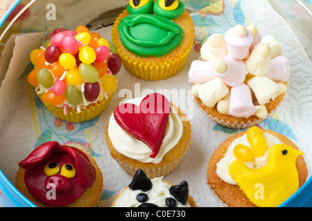 A variety of vibrant fun homemade cup cakes stored in a tin. - Stock Photo