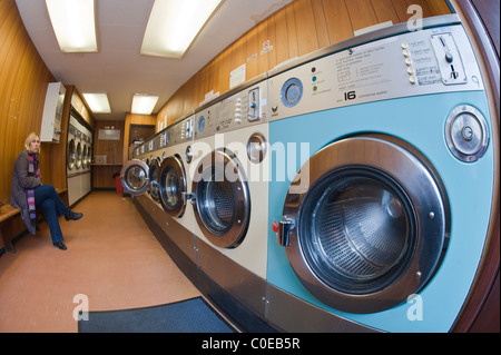 A laundrette with commercial washing machines and a MODEL RELEASED woman waiting for her washing in the background - Stock Photo