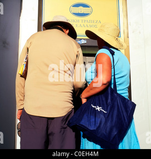 A middle-aged couple tourists getting money out from an ATM cash machine Santorini, Greek Islands, Greece  KATHY - Stock Photo