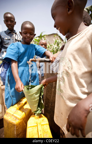 Girls filling water bottles at Rwandan village well. - Stock Photo