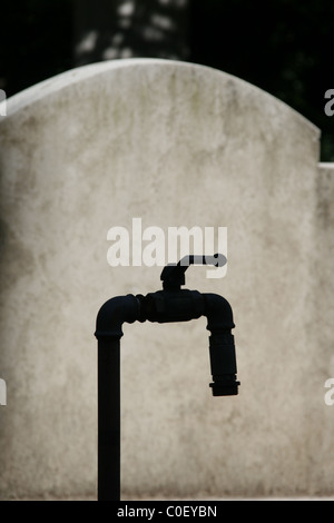 one single water tap outdoors in cemetery - Stock Photo