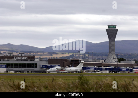 AIR TRAFFIC CONTROL TOWER, EDINBURGH AIRPORT, EDINBURGH, MID LOATHIAN, WITH PLANES ON THE RUNWAY - Stock Photo