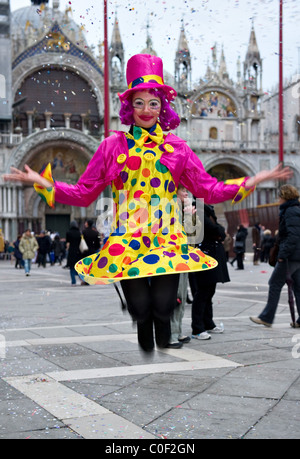A girl wearing a clown Carnival costume jumping in St Mark Square Venice Italy - Stock Photo