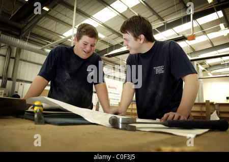 apprentice joiners looking at plans on bench - Stock Photo