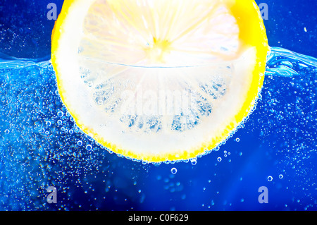 Close-up of a lemon slice with bubbles on blue - Stock Photo