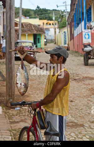 Man with a fish, Street with cobblestone, Oldtimer, Trinidad Cuba - Stock Photo