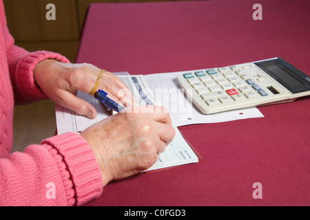 Close up elderly woman writing cheque and checking bank statement - Stock Photo