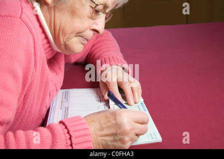 Close up elderly woman writing cheque to pay for propane gas - Stock Photo