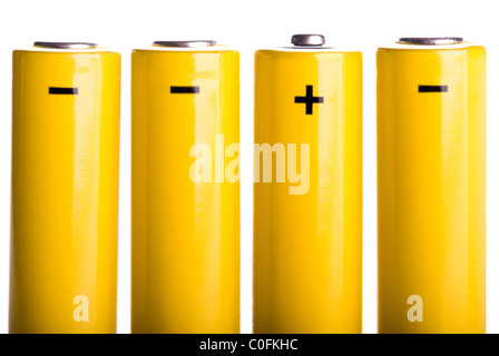 four yellow batteries with plus and minus standing - Stock Photo
