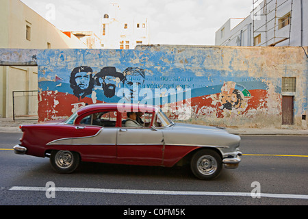 An old American 1950s automobile driving past a painted mural of Che Guevara in Havana  Cuba