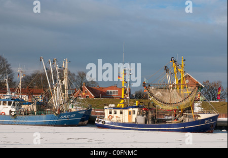 shrimp cutters in the harbour of Greetsiel, Northsea, in the background the dike, winterview - Stock Photo