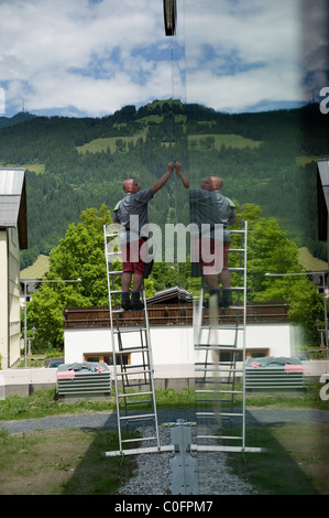 A male window cleaner up a ladder in the town of Kitzbuehel Tyrol, Austria - Stock Photo
