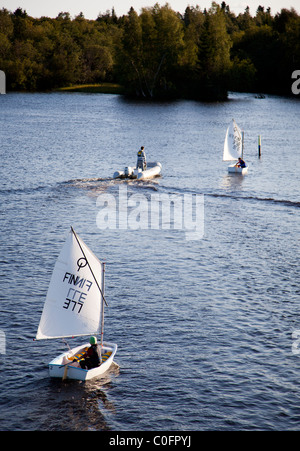 Young boy sailing alone with a small sailing boat , Finland - Stock Photo